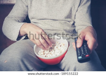 Young man is sitting on a sofa and eating popcorn while watching television - stock photo