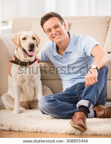 Young man is sitting on the floor with his dog and smiling. - stock photo