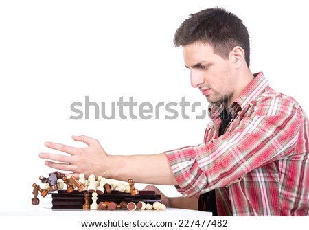 Young man is throwing chess from chess board on the white background. - stock photo