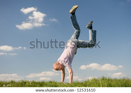 Young man is turning a cartwheel. Lifestyle picture - stock photo