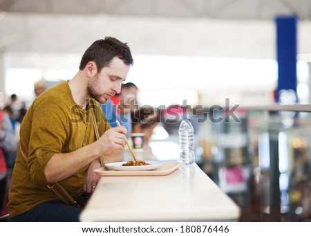 Young man is waiting at the airport for his flight . He is having a snack at the restaurant. - stock photo
