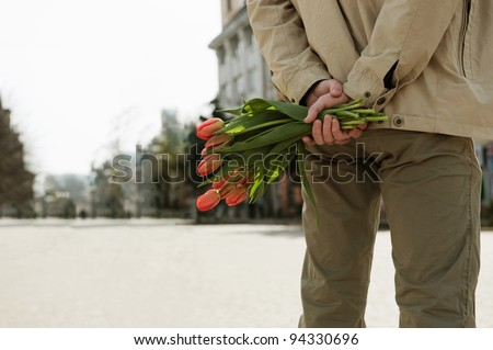 Young man is waiting for his girlfriend with tulips - stock photo