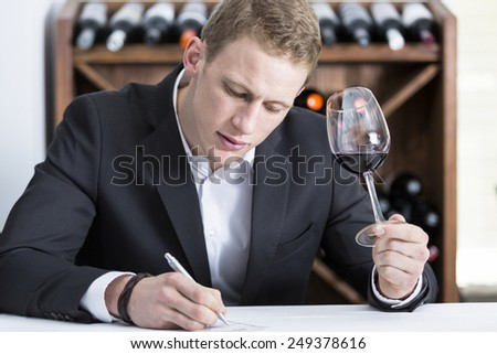 young man is writing down on a wine tasting sheet on a wine tasting session holding a red wine glass at a restaurant - focus on the man face - stock photo