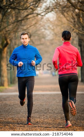 Young man jogging in park, woman running in opposite direction - stock photo