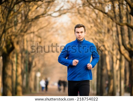 Young man jogging in tree alley - late autumn - stock photo