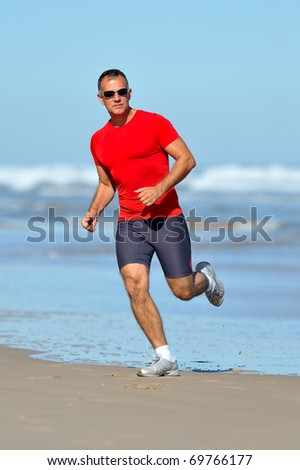 young man jogging on the beach in summer - stock photo