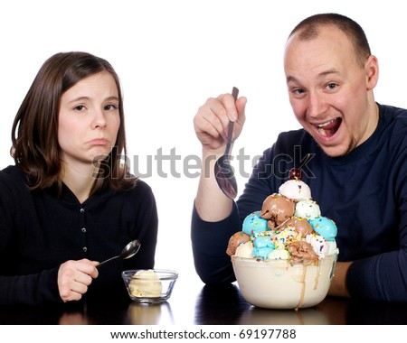 Young man joyously starts to dig in to a giant bowl of multi-flavored scoops of ice cream. Meanwhile his wife frowns as she only has one small single scoop of vanilla ice cream.