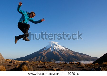 Young man jumping above the volcano - stock photo