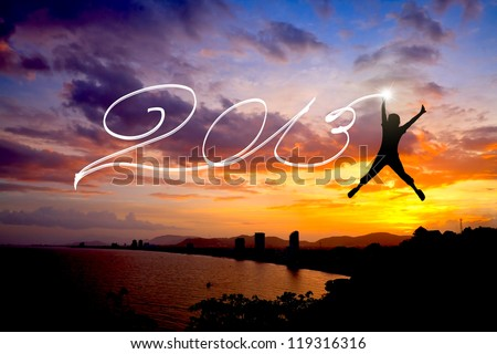 Young man jumping and drawing 2013 before sunrise sky