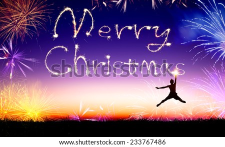 young man jumping and drawing the merry christmas - stock photo