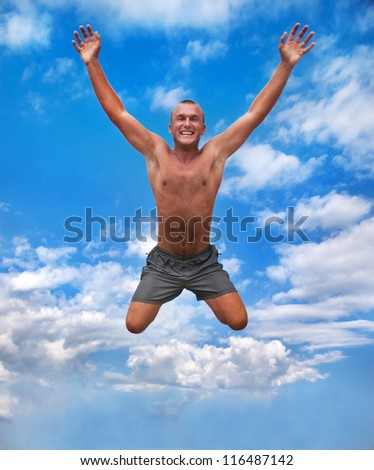 young man jumping and raising hands in the air against a blue sky