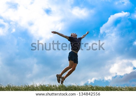Young man jumping high up to the sky - stock photo