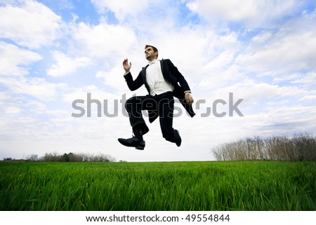Young man jumping in a field, wearing a tuxedo. - stock photo