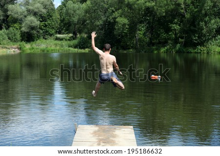 Young man jumping into lake  - stock photo