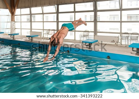 Young Man Jumping Into The Water Swimming Pool - stock photo