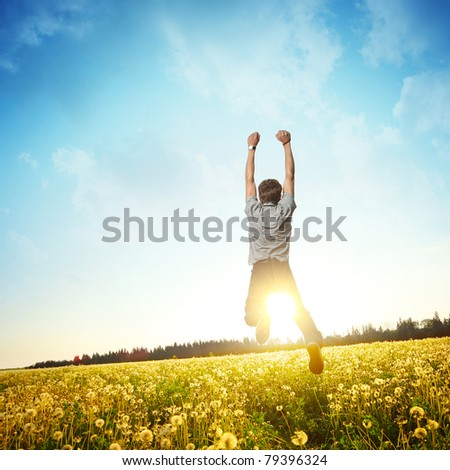 Young man jumping on meadow with dandelions on cloudy background - stock photo