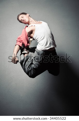 Young man jumping. On stone wall background.