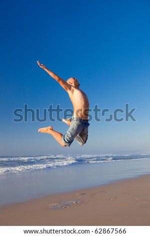 Young man jumping on the beach - stock photo