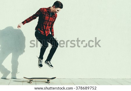 Young man jumping on the skateboard on the city street - stock photo