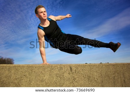 Young man jumping over wall on obstacle course - stock photo