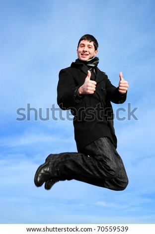 Young man jumping thumbs up - stock photo
