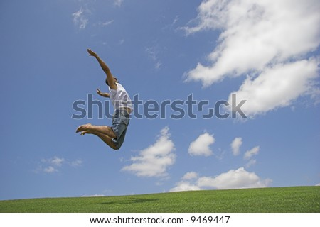 Young man jumping very high on a green meadow - stock photo