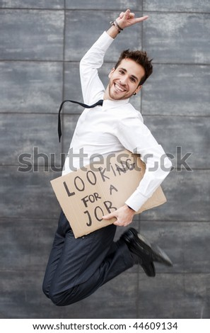Young man jumping with a Looking for a job sign - stock photo