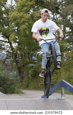Young man jumping with bike over ramp - stock photo
