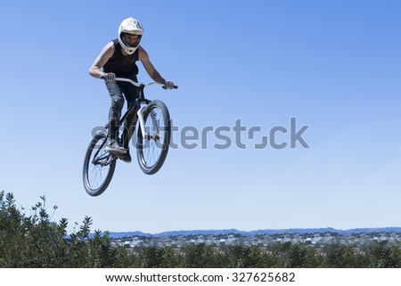 young man jumping with BMX bike on a BMX session in the mountain - focus on the body - stock photo