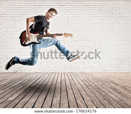young man jumping with electric guitar on a room - stock photo