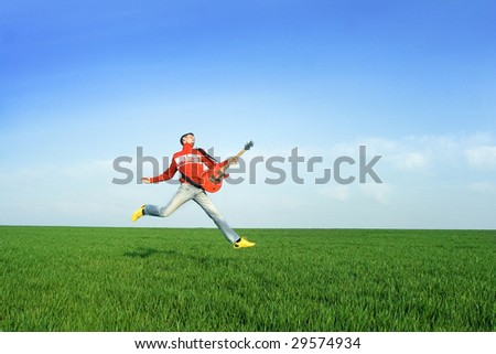 Young man jumping with guitar i meadow - stock photo