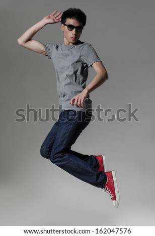 Young man jumping with sunglasses isolated over a gray background
