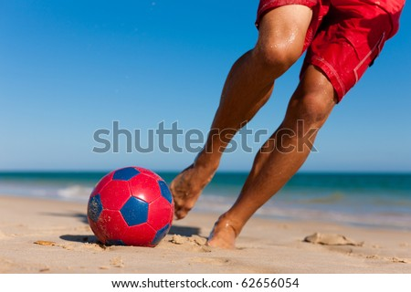 Young man (just feet) on the beach playing soccer in his vacation, he is about to kick the ball - stock photo