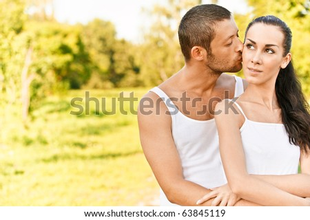 Young man kisses in on cheek beautiful dark-haired woman, against summer solar park.