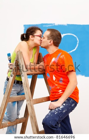 Young man kissing his girlfriend during home renovation