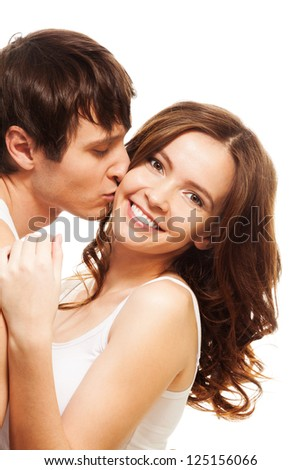 Young man kissing his happy smiling girlfriend isolated on white - stock photo