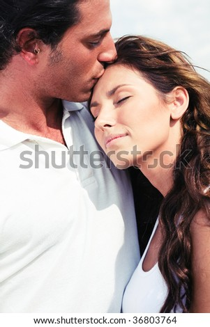 Young man kissing on forehead - stock photo