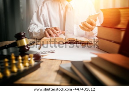 Young man lawyer give suggestion mobile customer and reading the lawyer book for legislation issue to help afflicted people, front view photography with vintage picture style and sunlight effect. - stock photo
