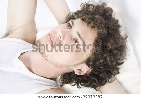 Young man lays on the bed - stock photo