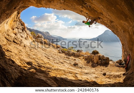 Young man lead climbing in cave with beautiful view in background