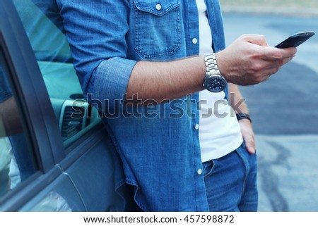 Young man leaning on his car, using a smart phone, Dressed casually. Flare light and vintage post processed. Urban life style, technology, shopping, roadside assistance and job hunting concept.