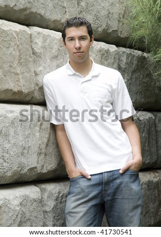 Young Man Leaning On Stone Wall - stock photo