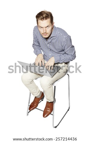 Young man leaning over the keyboard. Facial Expression. - stock photo