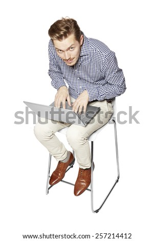 Young man leaning over the keyboard on his knees. - stock photo