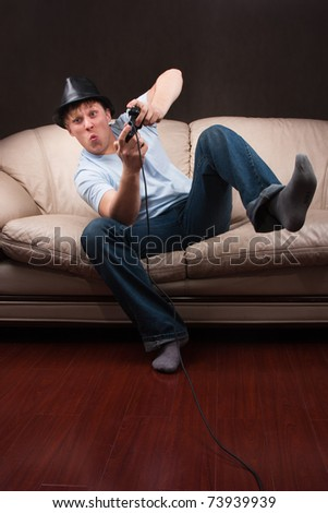 young man leaning while playing video games on gray background - stock photo