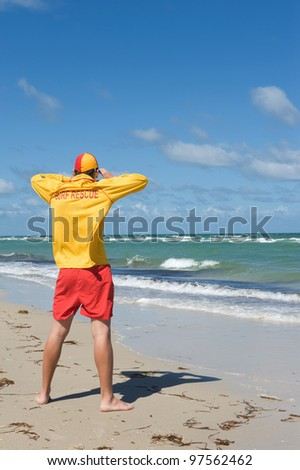young man  life saver  watching the situation on the sea - stock photo