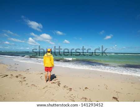 Young man  life saver  watching the situation on the sea.Wide angle - stock photo
