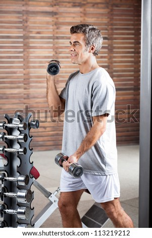 Young man lifting dumbbells in health center - stock photo
