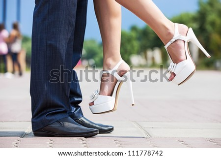 Young man lifting his bride up outdoors, close-up of lower part of the bodies - stock photo