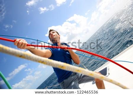 Young man lifting the sail of catamaran during cruising - stock photo